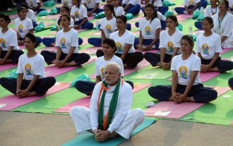 Indian Prime Minister Narendra Modi (C) participates in a mass yoga session along with other Indian yoga practitioners to mark the International Yoga Day on Rajpath in New Delhi on June 21, 2015.  Prime Minister Narendra Modi on June 21 hailed the first International Yoga Day as a